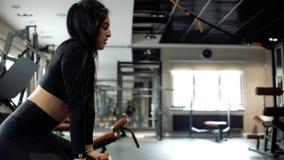 Athletisches kaukasisches Mädchen mit dem brunette Haar, das auf einem geeigneten Ball in der Turnhalle sitzt stock footage