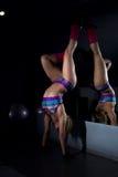 Athletisches Mädchen, das auf den Händen des Spiegels steht Stockfotografie