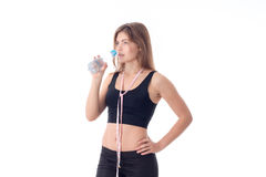 Athletisches Mädchen, das eine Flasche hält und geht, etwas Wasser zu trinken Lizenzfreies Stockfoto