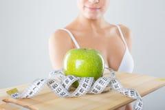 Athletisches Mädchen, das einen Behälter des grünen Apfels hält Stockfoto
