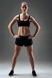 Athletisches Mädchen, das ihre Muskeln auf einem grauen Hintergrund demonstriert Stockfoto