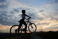 Athletisches Mädchen der Seitenansicht im Sturzhelm mit Fahrrad auf Felsen unter schönem Abendhimmel mit Wolken Lizenzfreie Stockfotos
