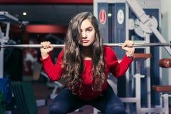 Athletisches Mädchen duckt sich mit einem Barbell Schönheit, die körperliche Bewegungen in der Turnhalle tut Sporteignung stockbild
