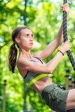 athletisches M?dchen engagiert auf einem Drahtseil auf dem Spielplatz lizenzfreie stockfotografie