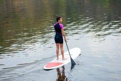 Athletisches Mädchen im Taucheranzugtraining in schaufelndem Wassersport stockfoto
