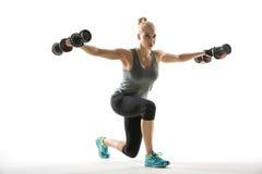 Athletisches Mädchen trainiert mit Dummköpfen Lizenzfreies Stockbild