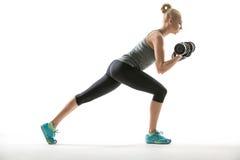 Athletisches Mädchen trainiert mit Dummköpfen Lizenzfreie Stockfotos