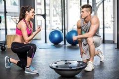 Athletisches Mannausarbeiten geholfen von der Trainerfrau Stockfotografie