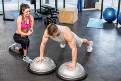 Athletisches Mannausarbeiten geholfen von der Trainerfrau Stockbilder