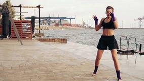 Athletisches Schattenboxen der jungen Frau durch das Meer Schönes weibliches Boxertraining auf dem Strand morgens, werfend stock video footage