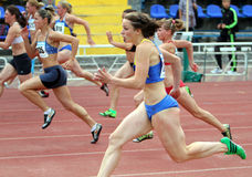 Athlets concurreert in 100 meters ras Stock Afbeeldingen