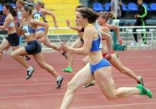 Athlets konkurrieren in 100 Metern Rennen Stockbilder