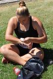 Athlète mis par tir féminin attachant du ruban adhésif à ses poignets Photo libre de droits