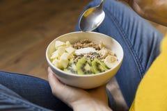Ating健康早餐碗 酸奶,荞麦,种子,在白色碗的新鲜水果在妇女` s手上 干净吃,节食,戒毒所 图库摄影