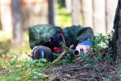 Atirador furtivo com a arma do paintball disfarçada na grama Foco sobre vagabundos Fotografia de Stock