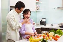 Atividade asiática dos pares na cozinha Imagem de Stock Royalty Free