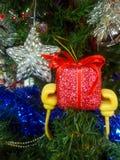 A atividade da família pôs a decoração colorida do Natal acima sobre a árvore verde foto de stock