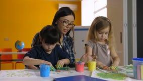 Atividade de pintura da mão que mantém crianças diversas ocupadas video estoque