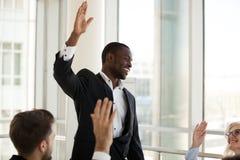 Atividade teambuilding da posse masculina preta do treinador com levantamento dos trabalhadores imagem de stock royalty free