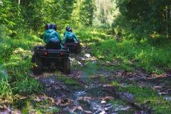 Atividades do verão para adultos - uma viagem no quadrilátero bikes na estrada suja Imagem de Stock