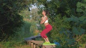 Atividades dos esportes, menina surpreendente que executa o exercício da ocupa dos esportes durante o exercício no ar livre na po filme