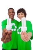 Ativistas ambientais que mostram ampolas de poupança de energia Fotografia de Stock