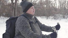 Ativo uma mulher idosa contratada no passeio nórdico com as varas no conceito saudável do estilo de vida da floresta do inverno m filme