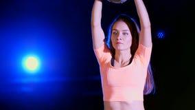 Atlética, bonito, a jovem mulher que faz a vária força exercita com pesos Na noite, à vista de colorido filme