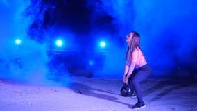 Atlética, bonito, a jovem mulher que faz a vária força exercita com pesos Na noite, à vista dos holofotes filme