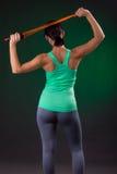 Atlética bonito, posição da mulher da aptidão, levantando com uma corda de salto em um fundo cinzento com um luminoso verde Imagens de Stock