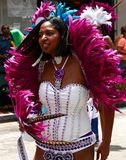 Atlanta Carnival Magenta feathers. A woman wearing a bikini outfit with magenta and blue feathers during a parade for Atlanta Caribbean Carnival 2014 Royalty Free Stock Photo