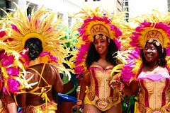Atlanta Carnival Yellow and Pink Girls 3. A group of women wearing a multi-colored outfits with yellow and pink feathers during a parade for Atlanta Caribbean Royalty Free Stock Photos