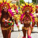 Atlanta Carnival Yellow and Pink Girls 2. A group of women wearing a multi-colored outfits with yellow and pink feathers during a parade for Atlanta Caribbean Royalty Free Stock Photography