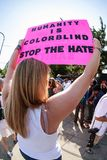 Woman Holds Up Sign At Atlanta Immigration Protest Rally. Atlanta, GA, USA - June 30, 2018: A woman holds a sign saying `Humanity is colorblind - Stop the hate royalty free stock photos