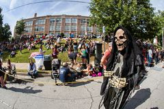 Person In Grim Reaper Costume Prepares For Atlanta Halloween Parade. Atlanta, GA, USA - October 21, 2017:  A person dressed as the grim reaper walks by a crowd Royalty Free Stock Photo