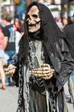 Person Wearing Grim Reaper Costume Prepares For Halloween Parade. Atlanta, GA, USA - October 21, 2017:  A person dressed in black as the grim reaper walks Stock Photography