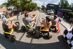 People Race Adult Big Wheels In Atlanta Fall Festival. Atlanta, GA, USA - September 23, 2017:  People race each other on adult big wheels in a friendly Stock Photos