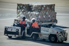 Dolly fleet operators at the Hartsfield-Jackson Airport. Atlanta, Georgia, USA - October 13, 2016: Dolly fleet operators with the dollies for baggage unit load Stock Image