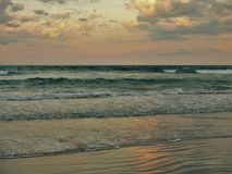 Atlantic Beach, North Carolina Sunset. Setting sun shines off of clouds and reflects off the sand and waves in Atlantic Beach, North Carolina Royalty Free Stock Photography