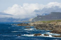 Atlantic coast. Atlantic waves break on the rocky coast of Achill Island in the west of Ireland, sheep graze on the cliff top and a heather covered mountain in Stock Photo