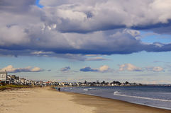 The Atlantic coast. USA. Maine. Atlantic Ocean. USA. Maine. The beach, with people watching the holiday houses on the beach. Beautiful sky with volumetric clouds Royalty Free Stock Photos