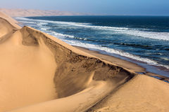 Atlantic coast of Walvis Bay, Namibia. South of Africa. Ocean surf with foamy waves. Jeep - safari through the huge sand dunes. The concept of extreme and royalty free stock images