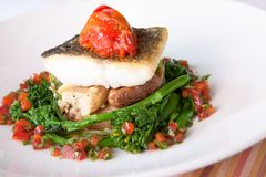 Atlantic Cod. Delectable Atlantic Cod served with fingerling scallion hash, braised rapini, saffron red peppers and bagna cauda sauce stock photography