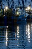 Atlantic Fishing Boats. Ocean going fishing boats at their pier in New Bedford Massachusetts, USA with their running lights reflecting off the water of the royalty free stock images