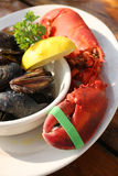 Atlantic Lobster Dinner. Fresh boiled Maine lobster on plate with muscles. Vertical format Stock Image