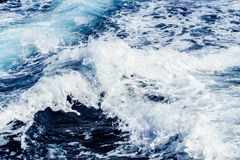 Atlantic ocean with blue water on a sunny day. Waves, foam and wake caused by cruise ship in the sea Stock Photography
