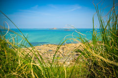 Atlantic ocean in Brittany, France. View of the Atlantic oseanthrough green grass Stock Photos