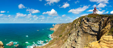 Atlantic ocean coast in Portugal. The lighthouse in Cabo da Roca. Cliffs and rocks on the Atlantic ocean coast in Sintra in a beautiful summer day, Portugal Royalty Free Stock Images