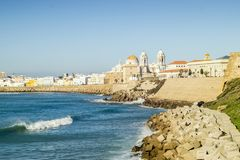 Atlantic Ocean shore and city center with Cathedral of Cadiz, An. Atlantic waves breaking on the urbanized shore of old Cadiz, Andalusia, Spain Stock Images
