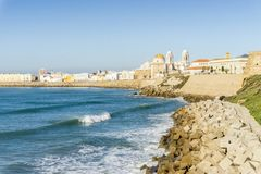 Atlantic Ocean shore and city center with Cathedral of Cadiz, An. Atlantic waves breaking on the urbanized shore of old Cadiz, Andalusia, Spain Royalty Free Stock Images